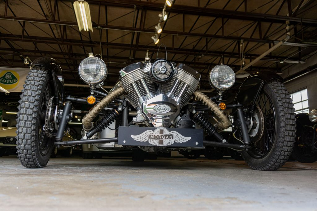 The front view of a 2012 Morgan 3-Wheeler in a car-filled garage