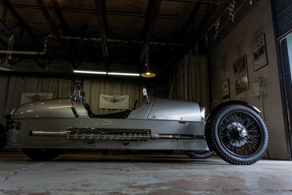 A low-angle side view of a silver 2012 Morgan 3-Wheeler in a garage