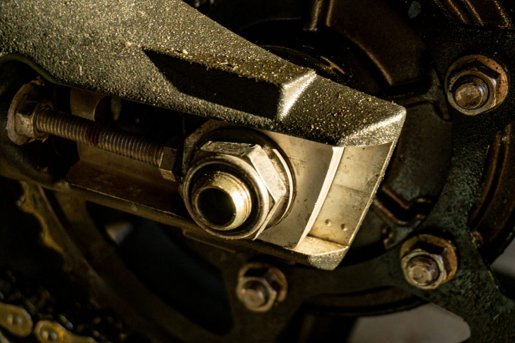 A close-up of a 2012 Triumph Street Triple R axle nut and chain adjuster with reference marks