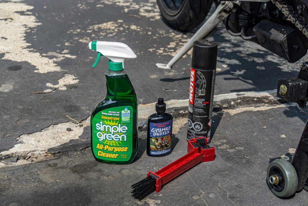 Cleaning solution, degreaser, motorcycle chain lube spray, and a motorcycle chain brush for cleaning and lubricating the chain