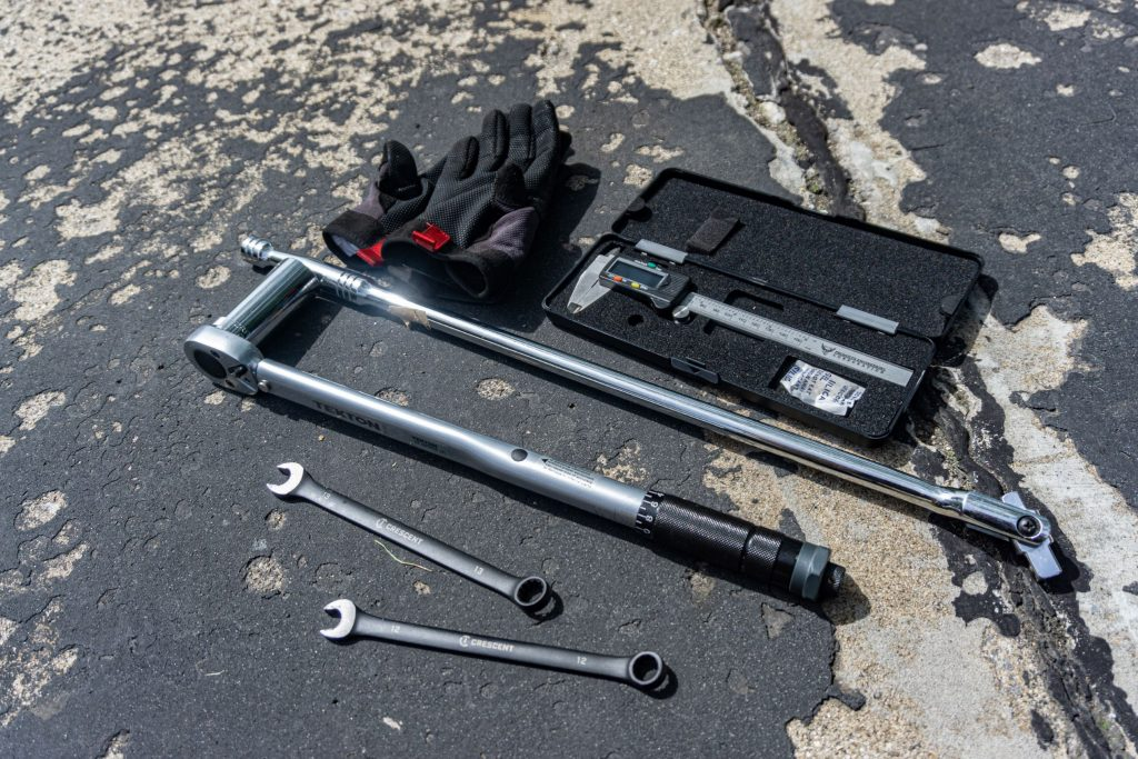 Digital calipers, a torque wrench, open-end wrenches, and mechanic gloves used to adjust the chain slack on a 2012 Triumph Street Triple R motorcycle