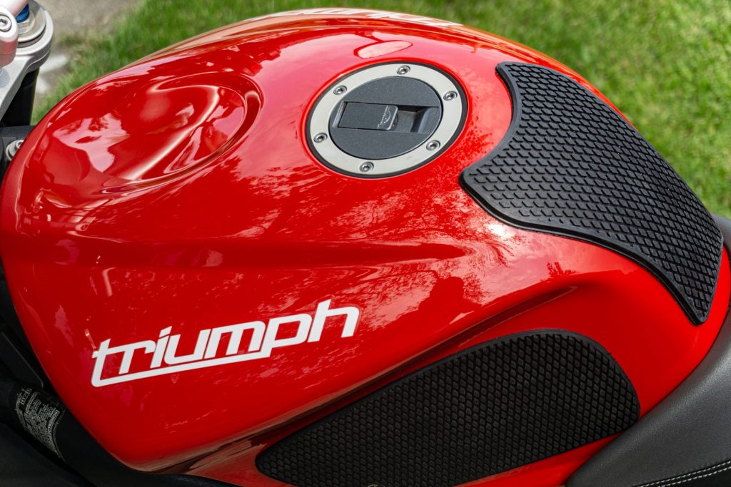An overhead left-side view of a red 2012 Triumph Street Triple R with black tank grips installed