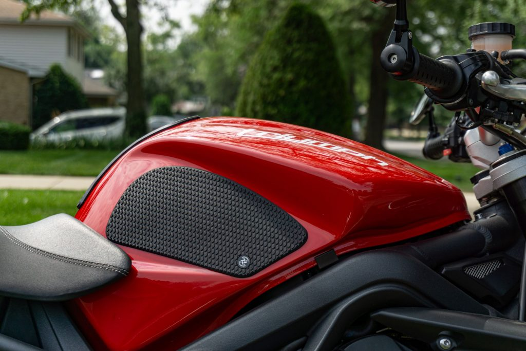 The right side of a red 2012 Triumph Street Triple R with black tank grips installed