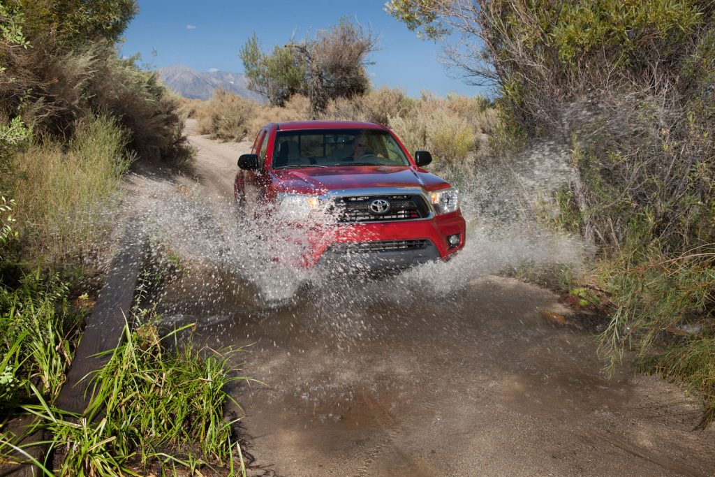 A red 2013 Toyota Tacoma driving through water