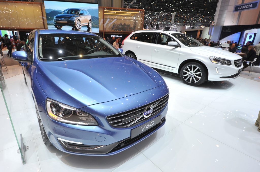 A white 2013 Volvo XC60 on display next to a blue V60 at the 38th Geneva Motor Show in March 2013