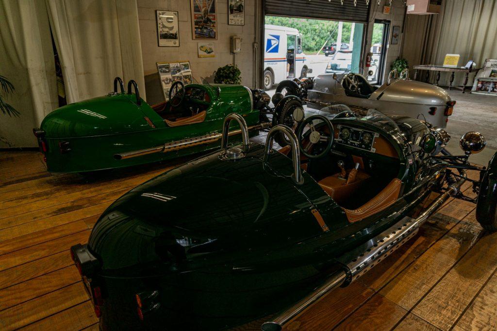 Two green 2013 Morgan 3-Wheelers in front of a silver 2012 Morgan 3-Wheeler in a garage