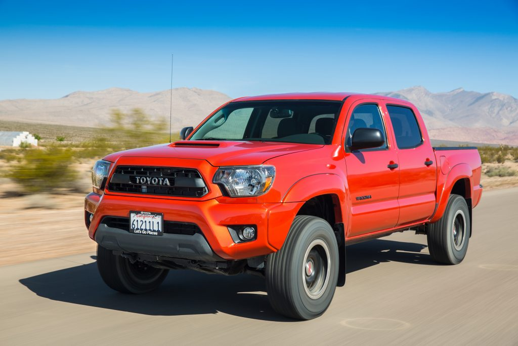 a bright red 2015 Toyota Tacoma TRD Pro off-road pickup truck driving on a sandy trail