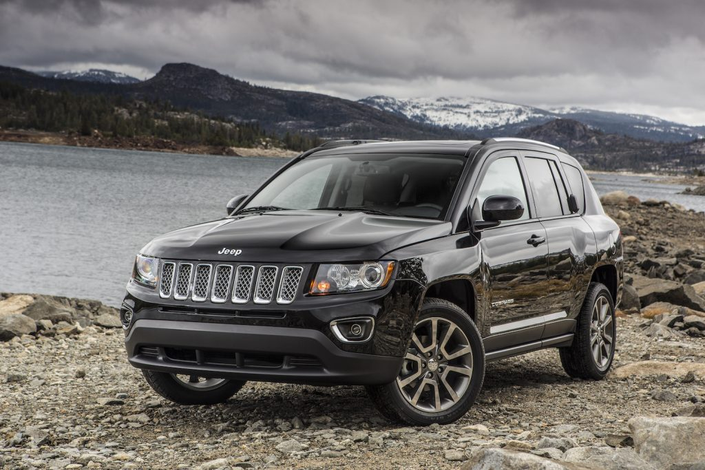 A 2016 Jeep Compass parked along a river with a mountainscape in the background