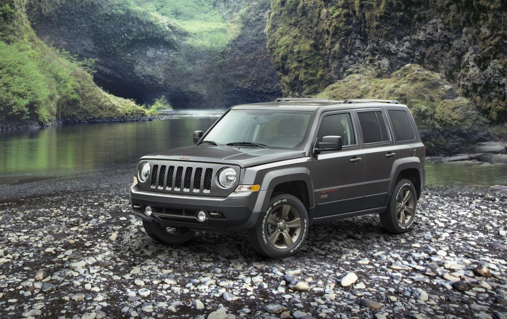 A grey 2016 Jeep Patriot parked along a river bed, the 2016 Patriot is one of the worst used cars you can buy
