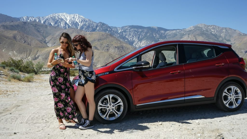 A pair of women gaze at a cell phone with a Chevy Bolt in the background