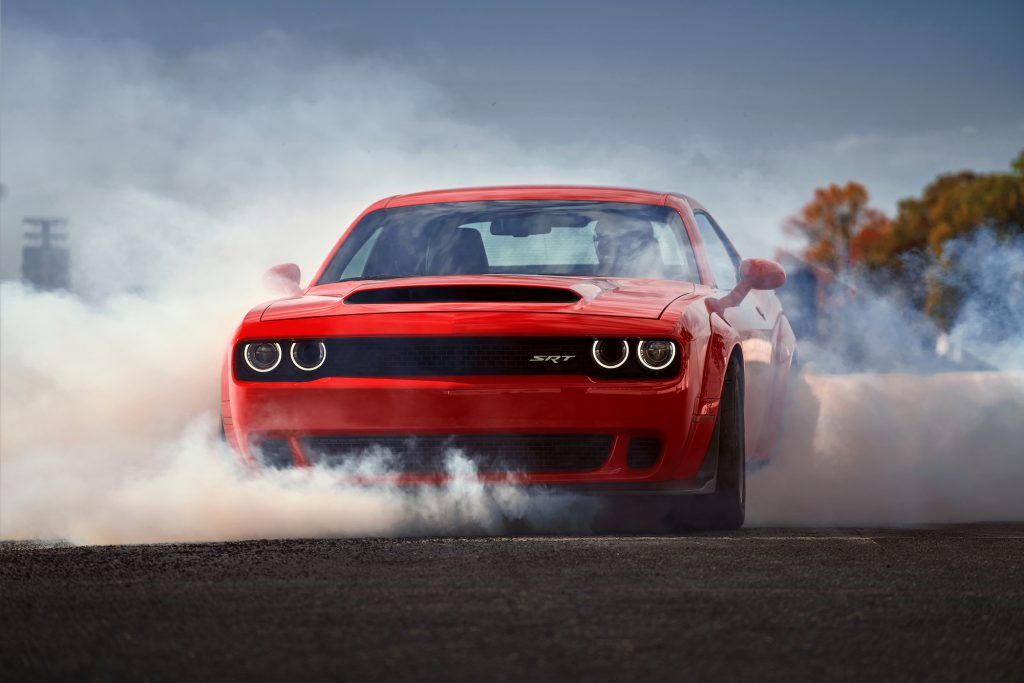 A red 2018 Dodge Challenger SRT Demon doing a burnout. The Demon is among the top fastest muscle cars of all time.