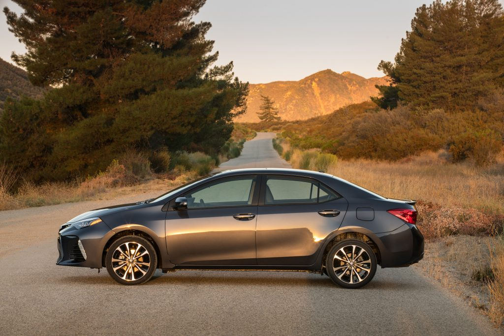 A dark gray metallic 2018 Toyota Corolla XSE parked on a country road surrounded by pine trees and mountains