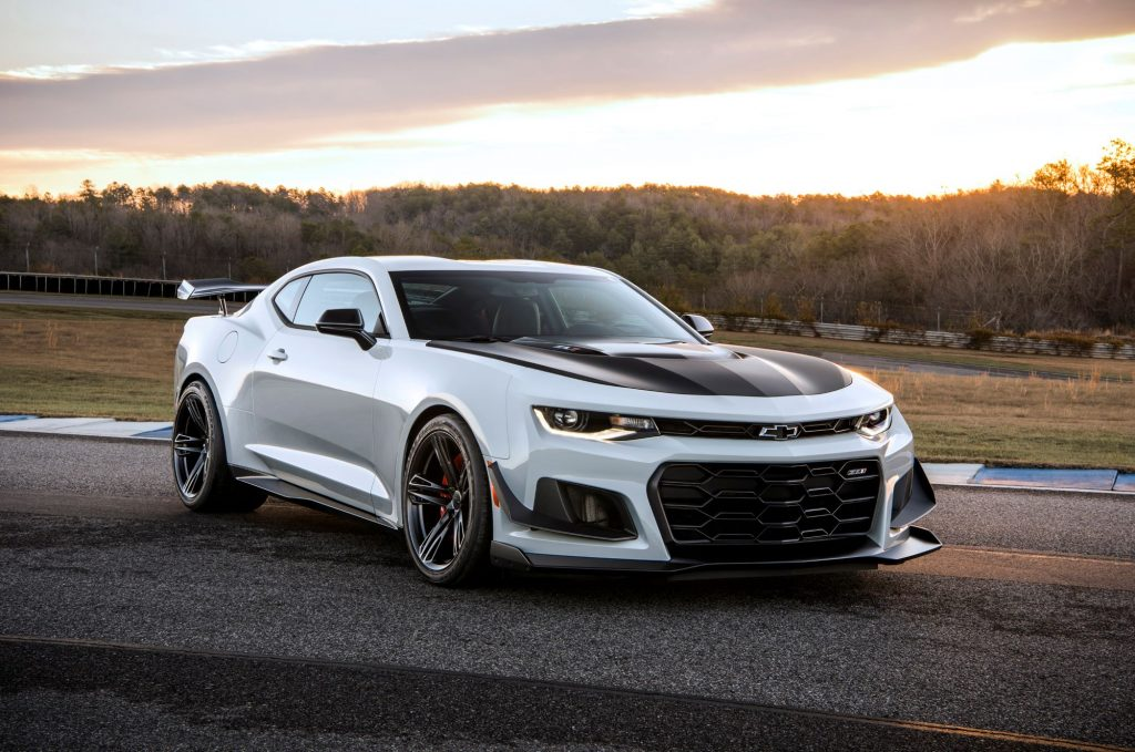 A silver Camaro with black racing stripes on the hood sitting on blacktop in a wooded area as the background.