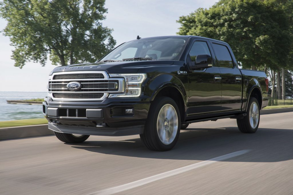 A 2019 Ford F-150 driving on a tree lined street, the 2019 Ford F-150 is the best used full-size truck under $25K and outranks the Chevy Silverado and the Ram 1500