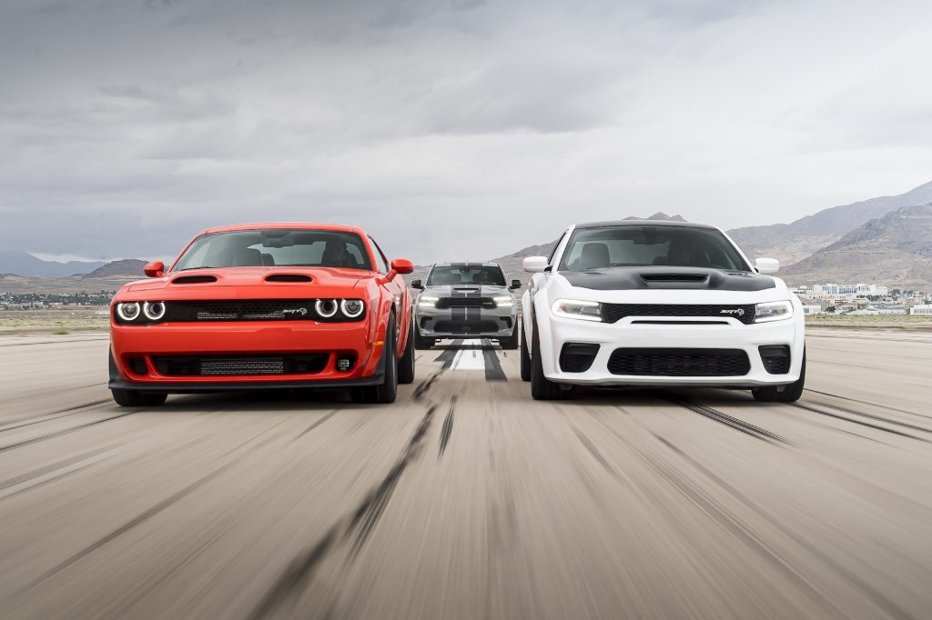 A red 2020 Dodge Challenger SRT Super Stock and a 2021 Charger SRT Hellcat Redeye race next to each other on a track with a 2021 Durango SRT Hellcat in the background