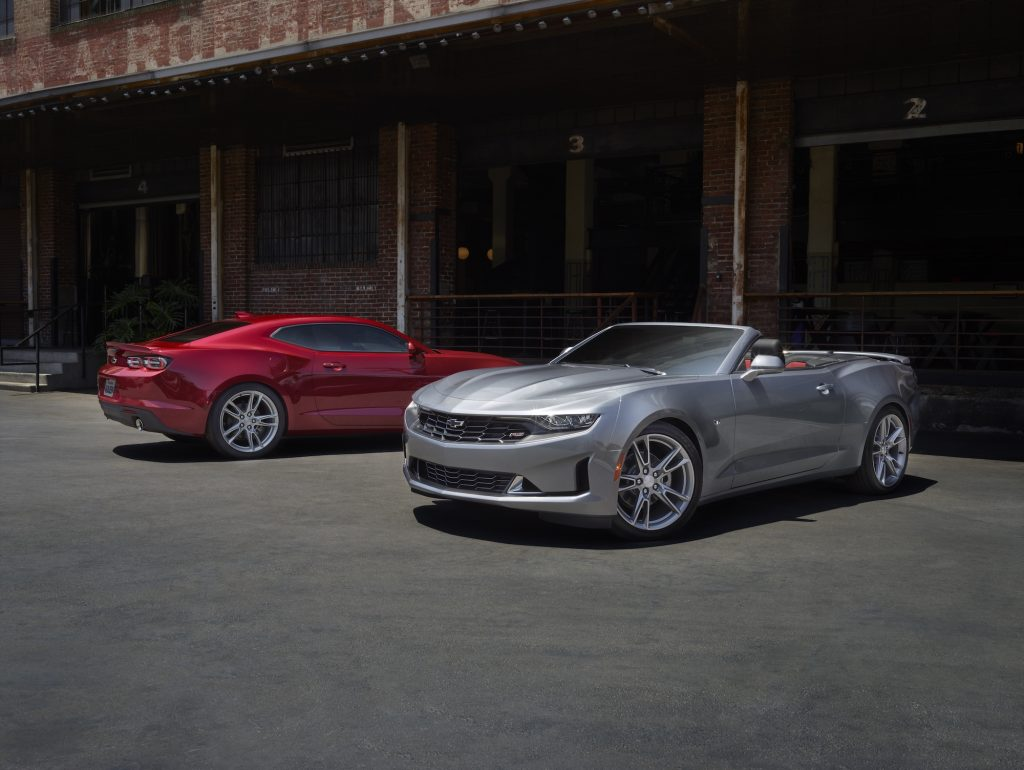 A red 2021 Chevy Camaro LS and a silver 2021 Camaro LT parked next to each other outside an old brick building