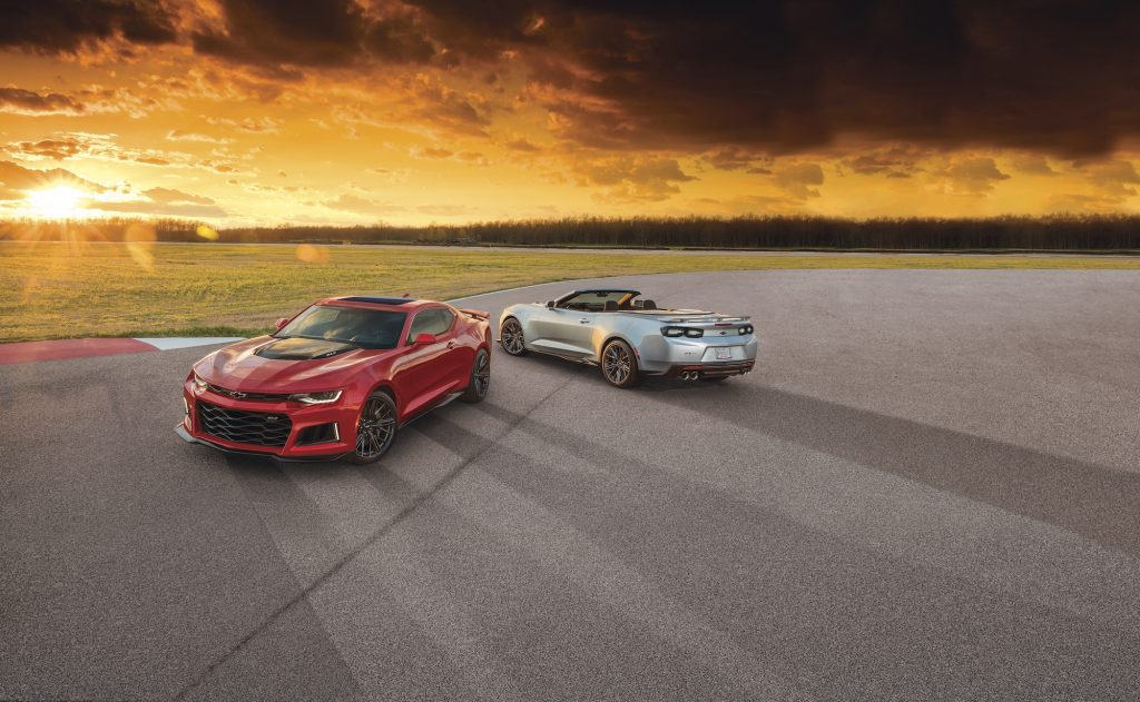 A red 2021 Chevy Camaro ZL1 coupe and silver ZL1 convertible parked on asphalt overlooking a large expanse of grass as the sun hangs low on the horizon