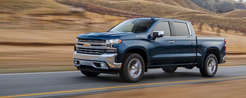 A dark blue 2021 Chevrolet Silverado drives through the desert.