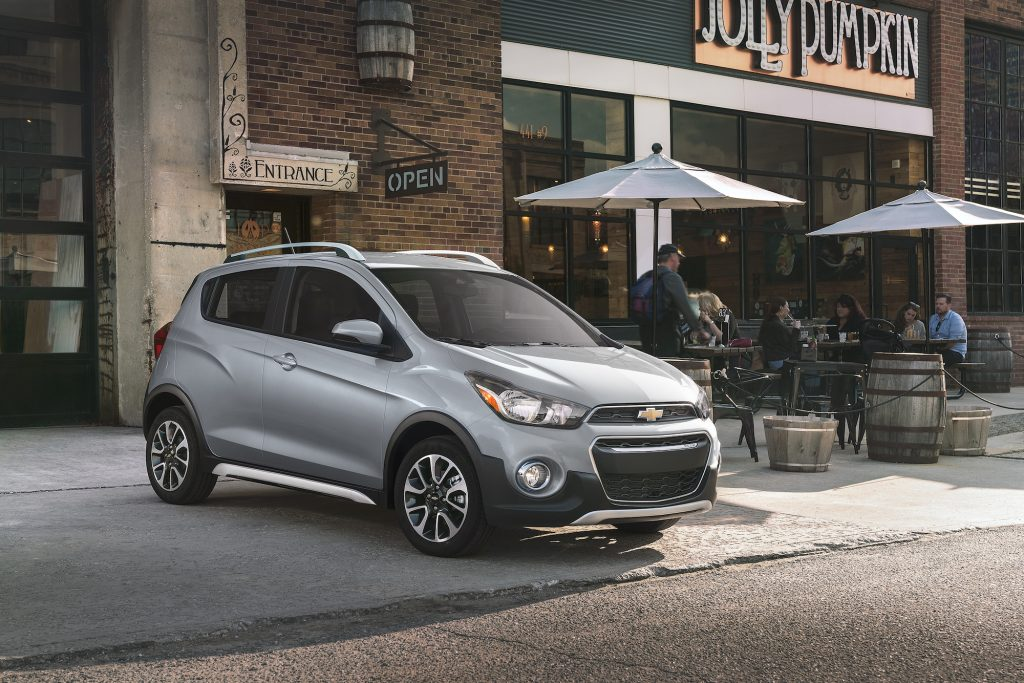 A silver 2021 Chevy Spark three-door hatchback parked outside a Jolly Pumpkin bakery and café