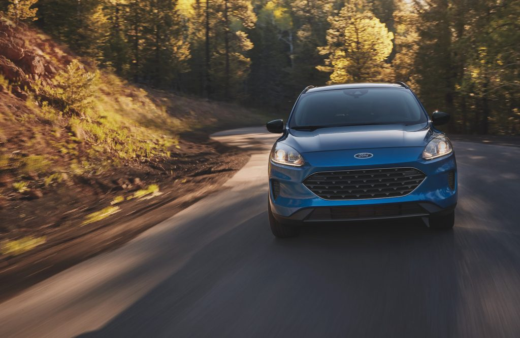 A blue metallic 2021 Ford Escape compact SUV travels on a tree-lined, sun-dappled country road