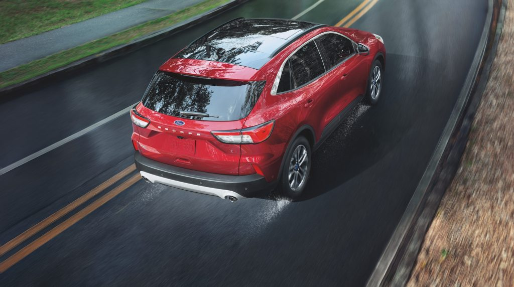 A red 2021 Ford Escape travels on a wet two-lane highway. The Ford Escape hybrid is one of five SUVs with the best gas mileage, according to CarGurus.