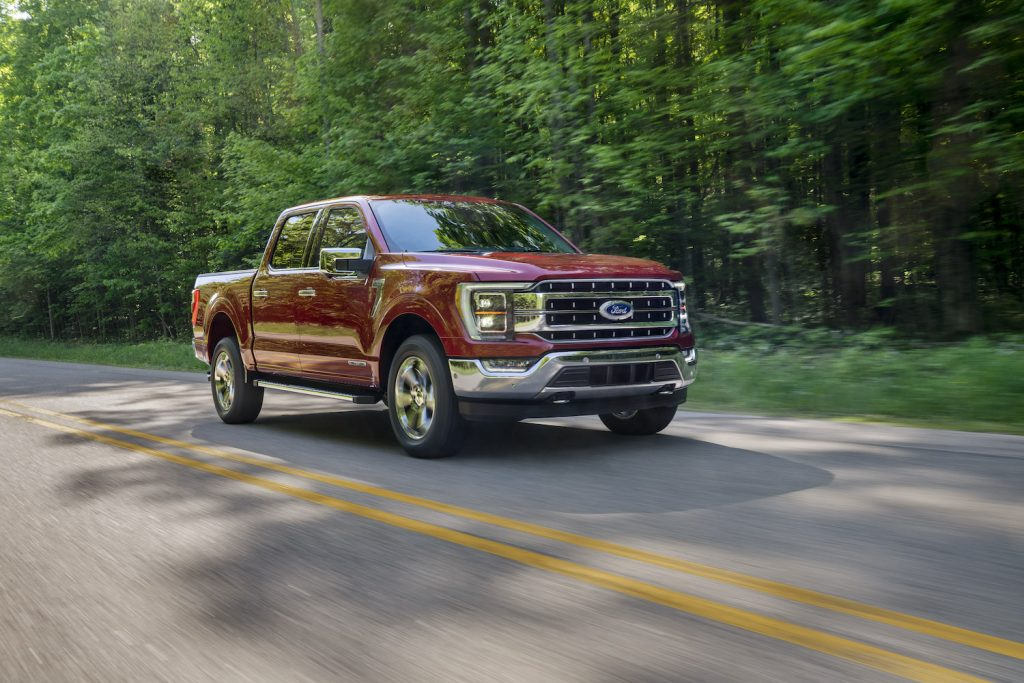 A red 2021 Ford F-150 driving, the latest Ford F-150 recall includes the truck's seatbelts