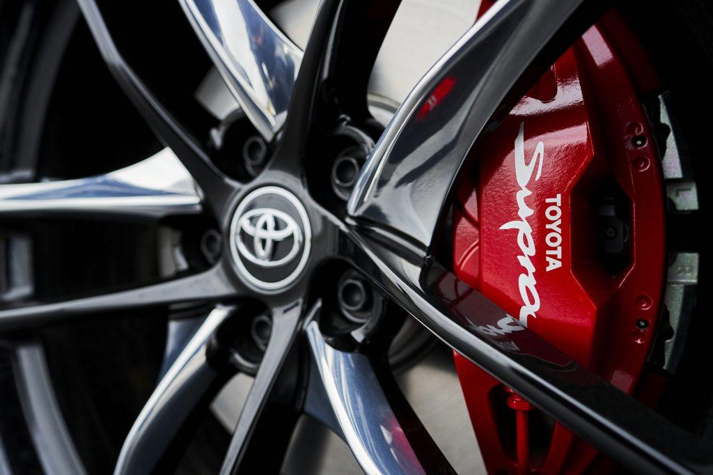 """A red Toyota brake caliper bearing the """"Supra"""" script"""
