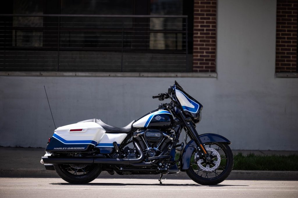 The side view of a white-blue-and-black 2021 Harley-Davidson Arctic Blast Street Glide Special in front of an old building