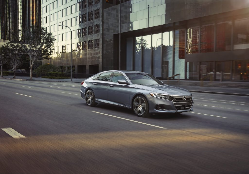 A silver 2021 Honda Accord driving in a city, the 2021 Honda Accord is a new midsize sedan and one of the best new cars for first-time buyers