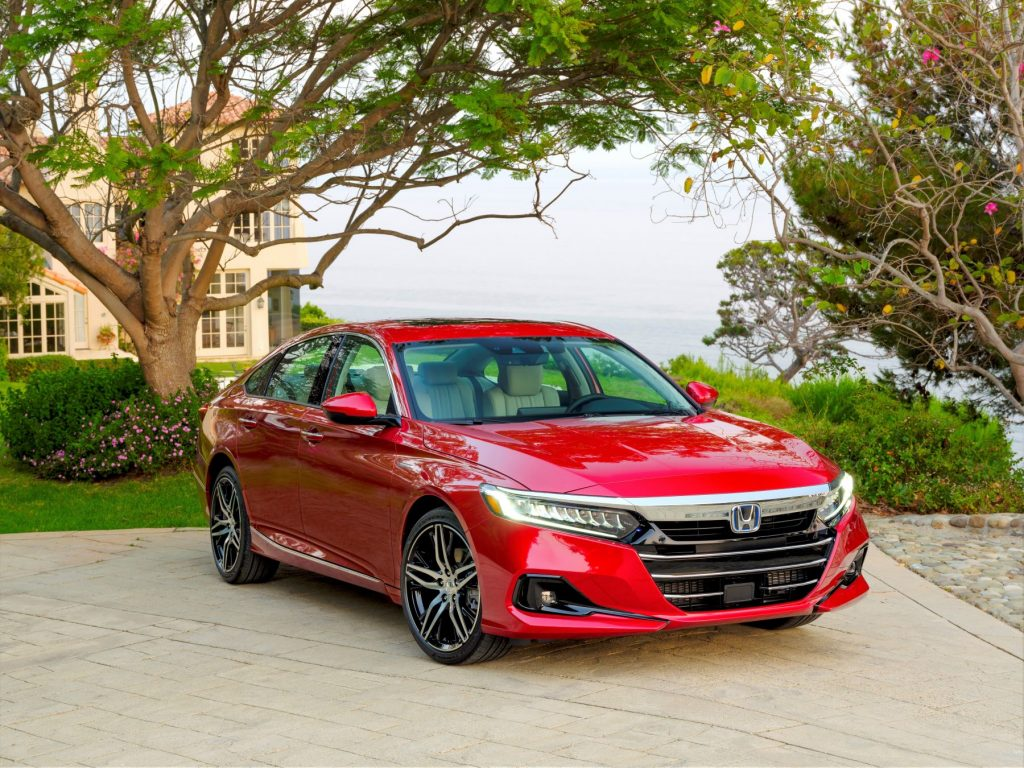 The 2021 Honda Accord Hybrid sedan in red parked outside of a luxury home near cobblestone