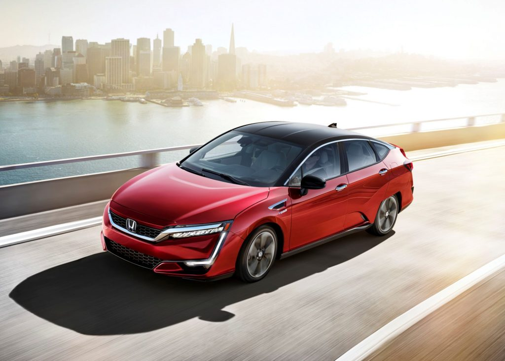 A red 2021 Honda Clarity Fuel Cell driving on a highway with an urban city in the background