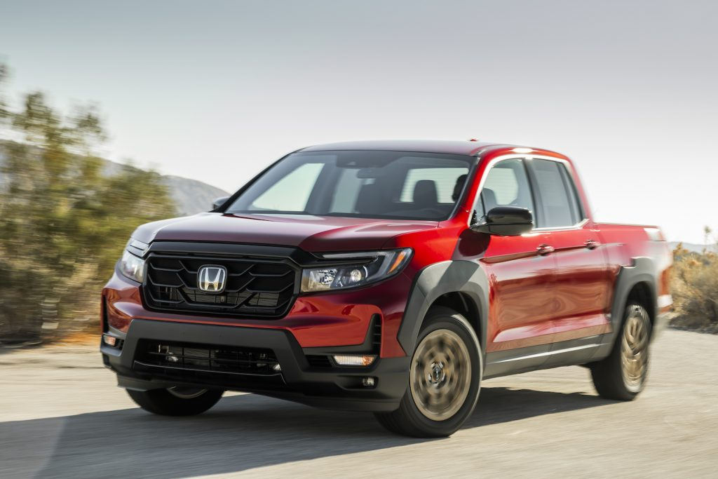 A red 2021 Ridgeline Sport with HPD Package driving on a sunny day, the Ridgeline is the best midsize truck of 2021