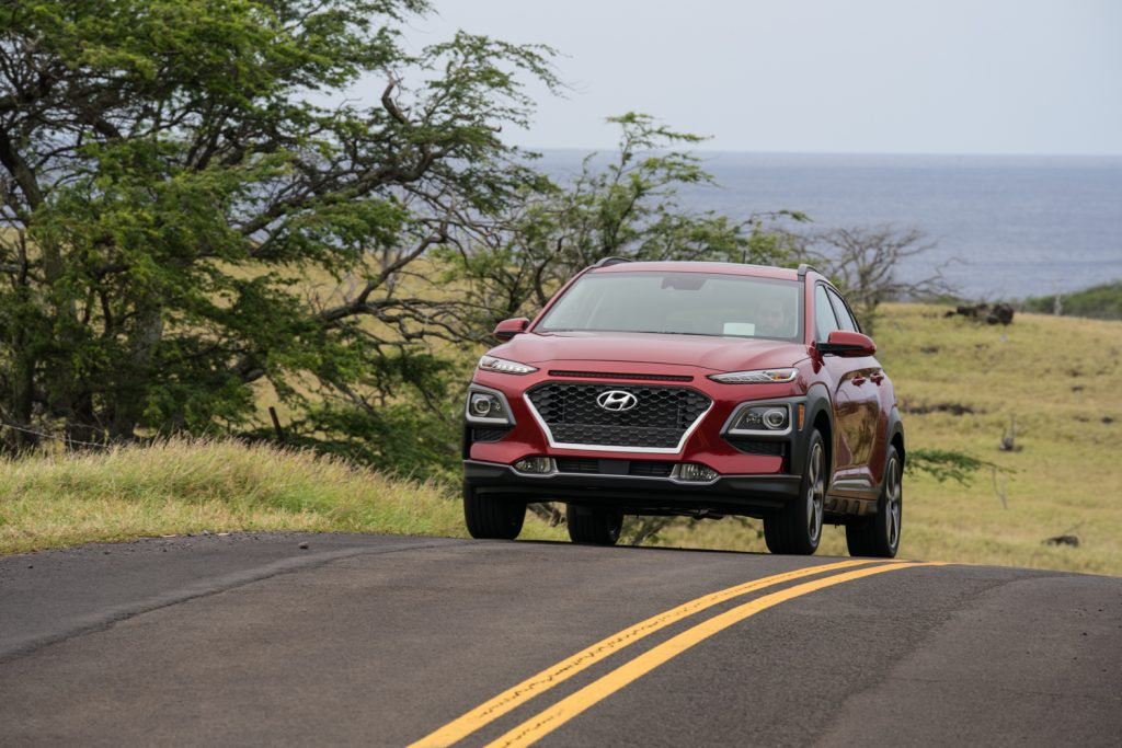 A red 2021 Hyundai Kona driving, the 2021 Hyundai Kona is one of the best commuter cars