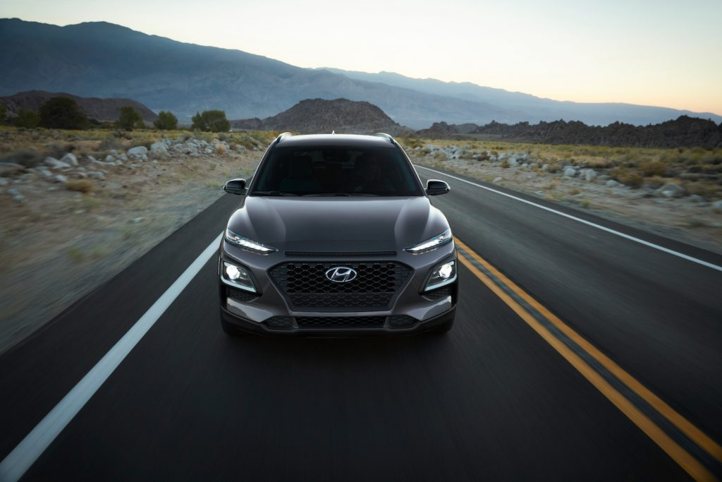 A grey 2021 Hyundai Kona EV driving on an empty road in the mountains