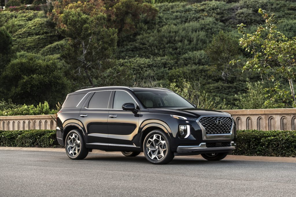 A black 2021 Hyundai Palisade midsize SUV parked along a concrete wall and shrubs on a hilllside