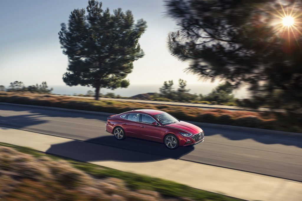 A red 2021 Hyundai Sonata driving by trees, the 2021 Hyundai Sonata is one of the least reliable Hyundai models