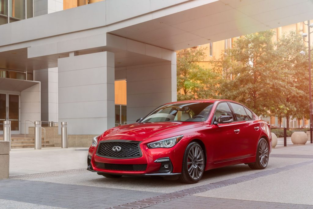 A red 2021 Infiniti Q50 sitting next to a modern style building in a wooded area.
