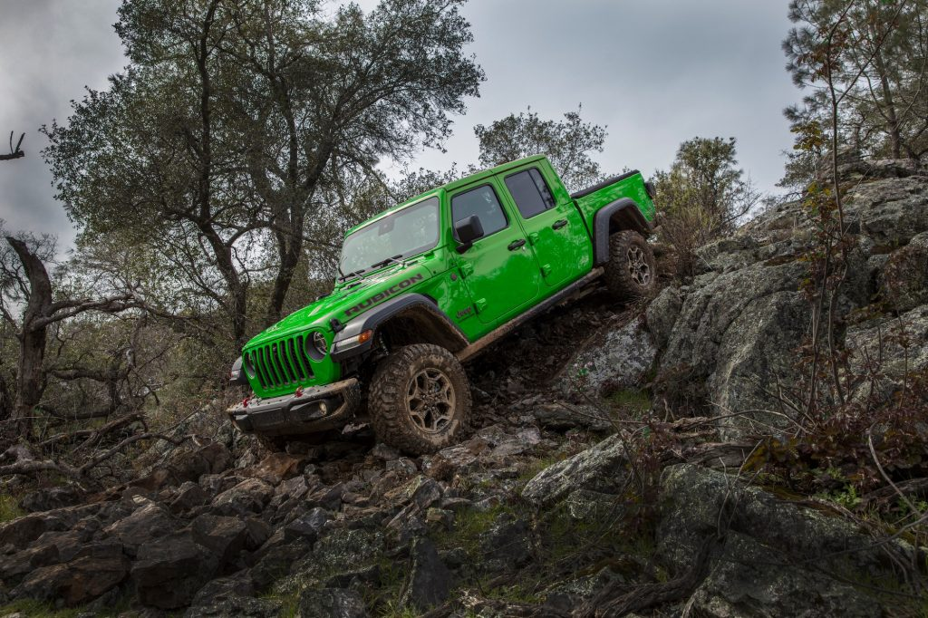 A 2021 Jeep Gladiator Rubicon in Gecko Green parked on the edge of a rocky incline on a cloudy day