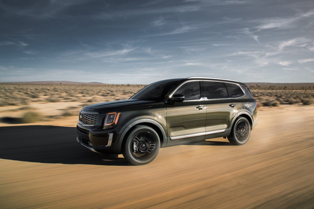 A green 2021 Kia Telluride driving over sand, the Kia Telluride is a new AWD SUV recommended by Consumer Reports