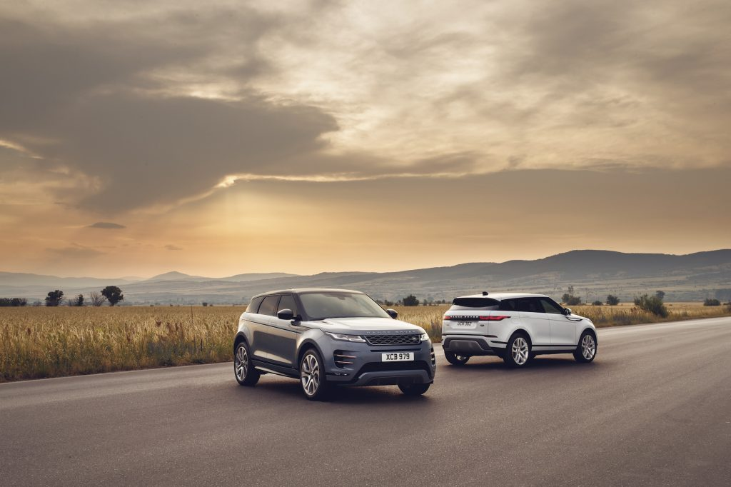 Two 2021 Land Rover Range Rover Evoque luxury compact SUVs parked on a road through a plain in front of mountains