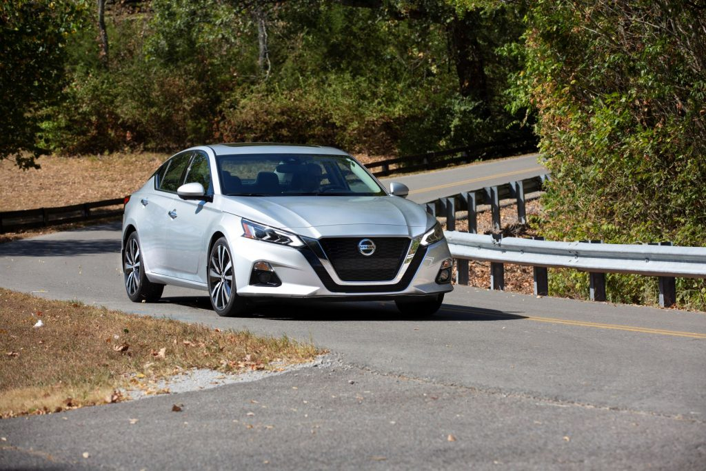 The 2021 Nissan Altima sedan in silver gray driving on a country highway