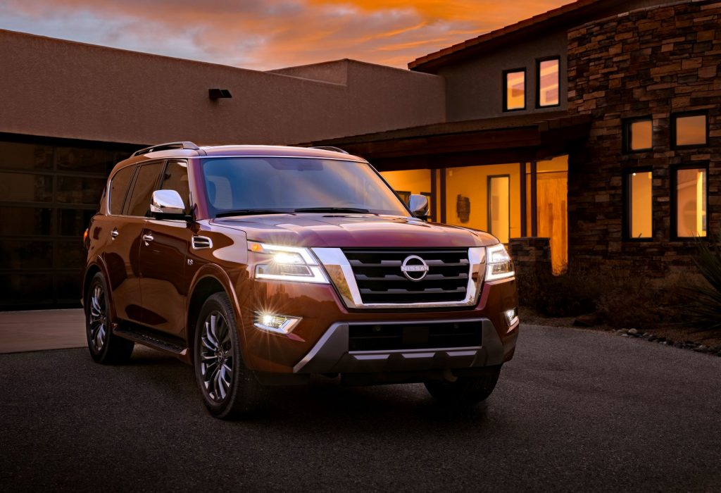 The 2022 Nissan Armada full-size SUV model in red parked outside of a house at sunset