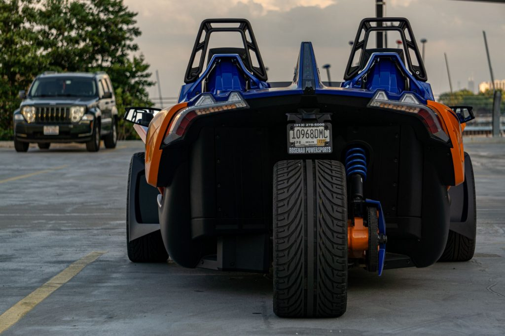 The rear view of an orange-and-blue 2021 Polaris Slingshot R in a parking lot with a Jeep SUV in the background