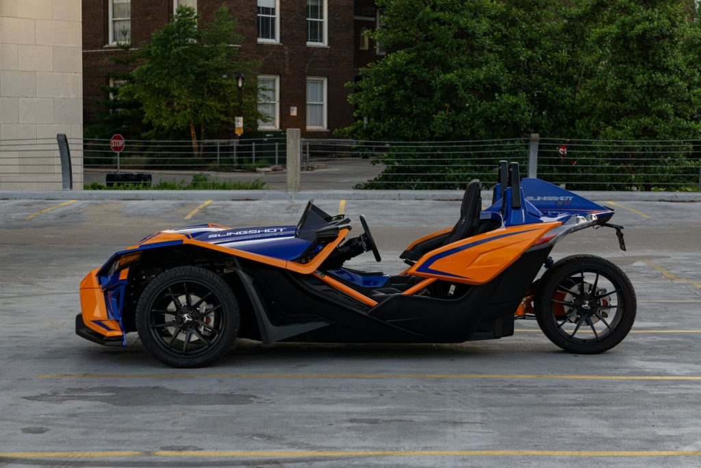 The side view of a blue-and-orange 2021 Polaris Slingshot R in a parking lot