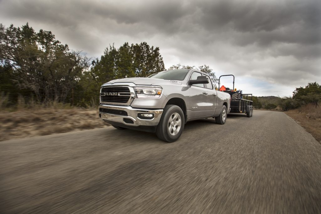 A silver 2021 Ram 1500 towing a heavy load