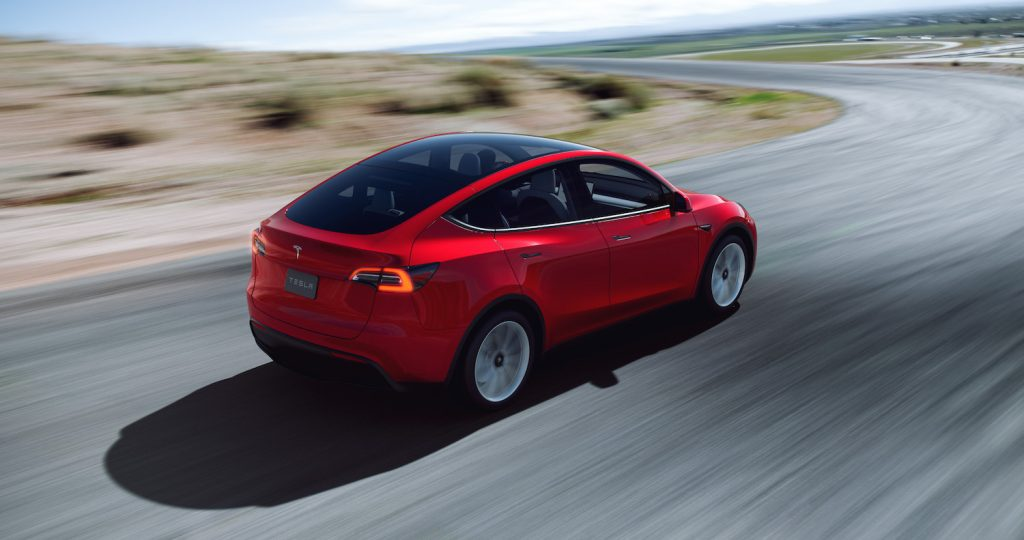 A red 2021 Tesla Model Y driving around a bend