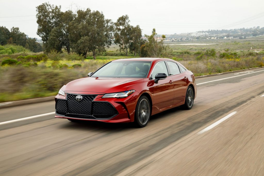 A red 2021 Toyota Avalon driving along a tree lined highway