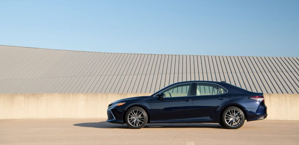 The 2021 Toyota Camry XLE sedan in dark blue parked near a concrete barrier