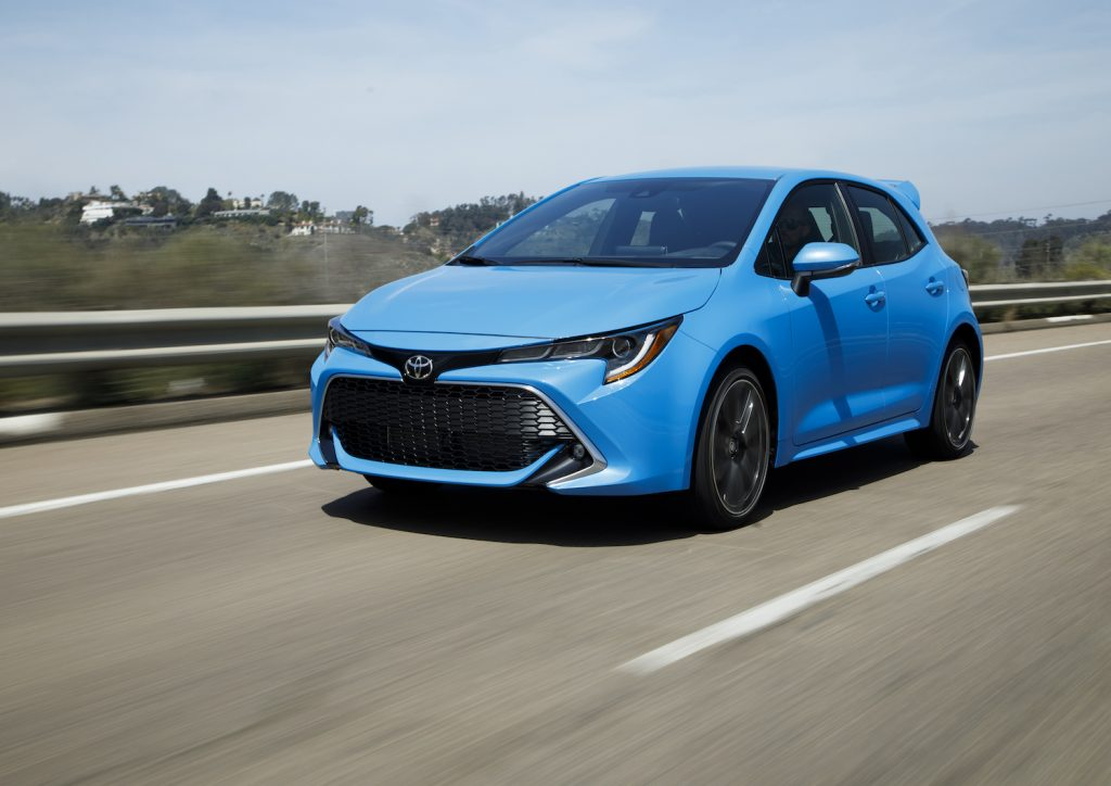 A blue 2021 Toyota Corolla Hatchback driving down an empty road, the 2021 Toyota Corolla Hatchback is one of the least reliable Toyota models
