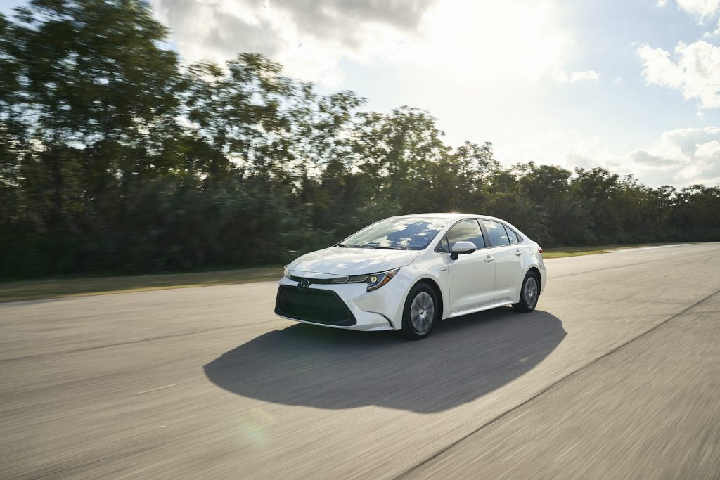 A white 2021 Toyota Corolla Hybrid driving, the 2021 Toyota Corolla Hybrid is a new sedan and is one of the most fuel-efficient new cars